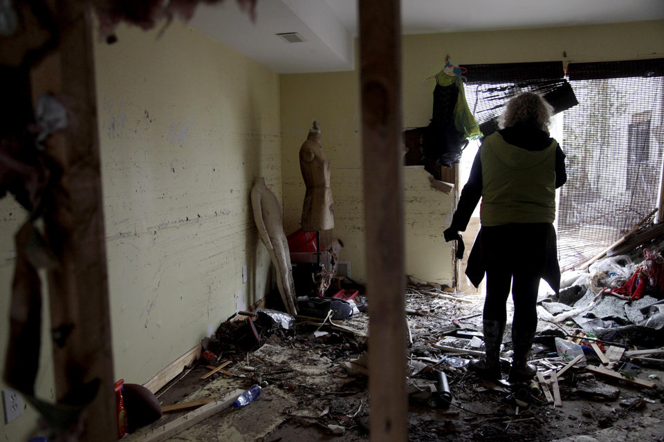 Photo -   Marina Sverdlov talks to a real estate broker while standing in her flood ravaged home in Staten Island, New York, Friday, Nov. 2, 2012. Sverdlov and her family are currently living with her mother in a one-bedroom apartment so they are trying to find an affordable rental as quickly as possible. (AP Photo/Seth Wenig)
