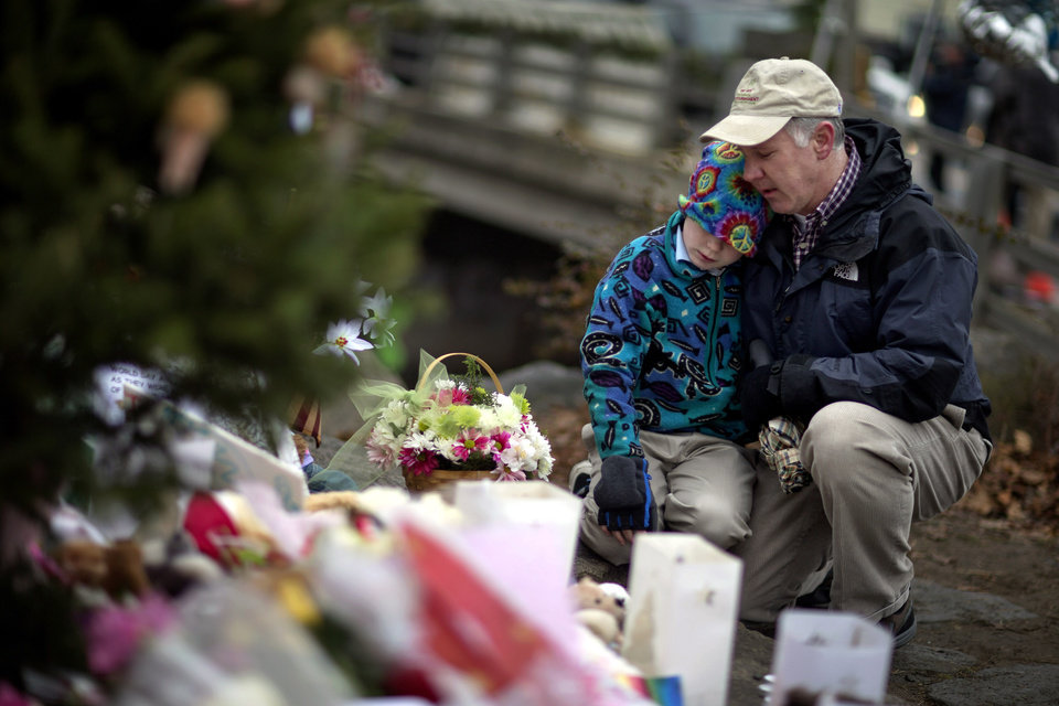 David Freedman, right, kneels with his son Zachary, 9, both of Newtown, Conn., as they visit a sidewalk memorial for the Sandy Hook Elementary School shooting victims, Sunday, Dec. 16, 2012, in Newtown, Conn. A gunman walked into Sandy Hook Elementary School in Newtown Friday and opened fire, killing 26 people, including 20 children. (AP Photo/David Goldman)