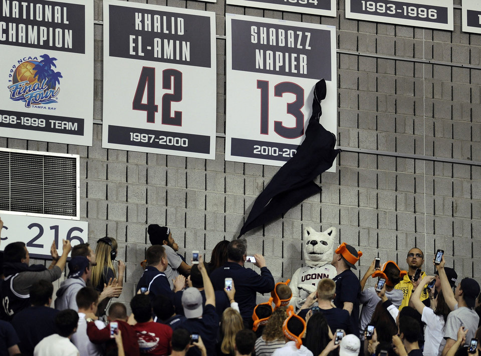 Photo - Carmen Velasquez, mother of Connecticut's Shabazz Napier, unveils her son's number on the Huskies Wall of Honor at a pep rally celebrating the the men's basketball team's NCAA championship, Tuesday, April 8, 2014, in Storrs, Conn. (AP Photo/Jessica Hill)