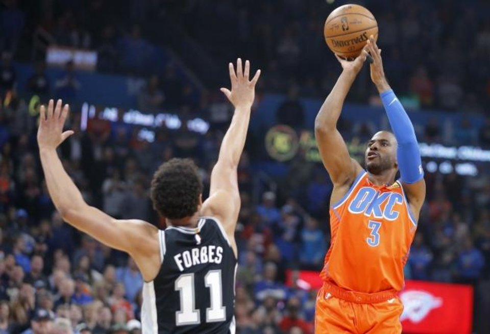Photo -  Oklahoma City's Chris Paul, right, shoots over San Antonio's Bryn Forbes during Sunday's game at Chesapeake Energy Arena. Paul was one of a team-record eight players to score in double figures as OKC whipped the Spurs 131-103. [Bryan Terry/The Oklahoman]