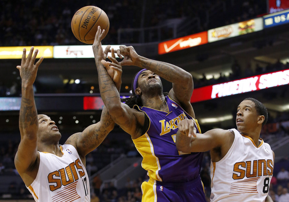 Photo - Los Angeles Lakers' Jordan Hill, middle, loses the ball as Phoenix Suns' P.J. Tucker, left, tips it away while Suns' Channing Frye (8) defends during the first half of an NBA basketball game Wednesday, Jan. 15, 2014, in Phoenix. (AP Photo/Ross D. Franklin)