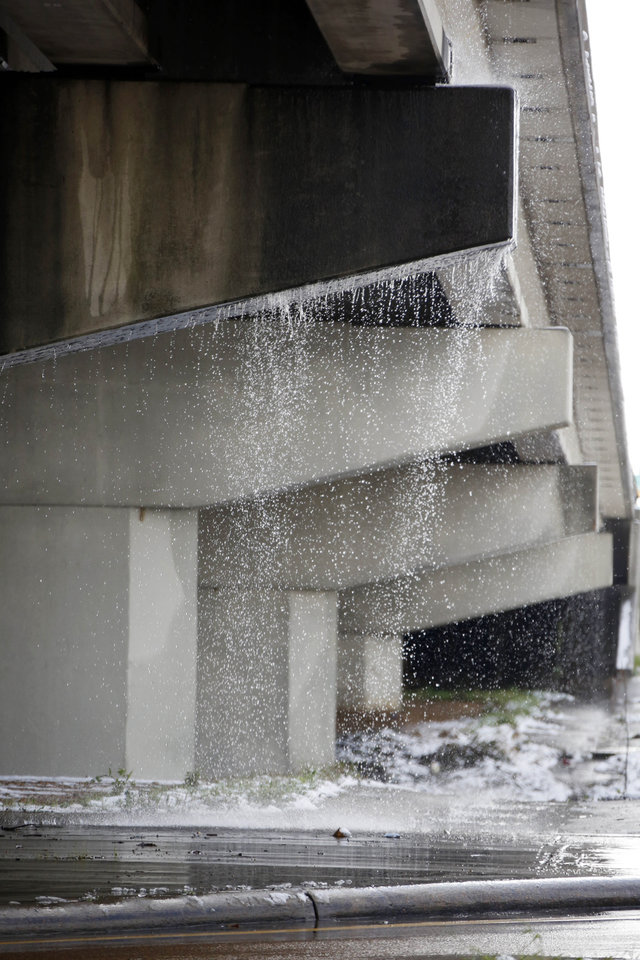 Photo - Runoff water from melting snow makes a waterfall from an overpass along I-55 in Jackson, Miss., Thursday,  Jan. 17, 2013.  A winter storm system left 2 to 4 inches of snow in parts of central Mississippi before heading east toward Alabama, the National Weather Service said. (AP Photo/Rogelio V. Solis)