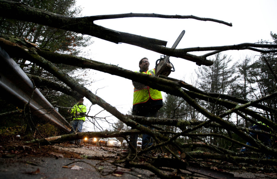 Photo - A worker cut a downed tree that fell on a road during the the early stages of Hurricane Sandy, Monday, Oct. 29, 2012, in Old Orchard Beach, Maine. Hurricane Sandy continued on its path Monday, as the storm forced the shutdown of mass transit, schools and financial markets, sending coastal residents fleeing, and threatening a dangerous mix of high winds and soaking rain. (AP Photo/Robert F. Bukaty) ORG XMIT: MERB107