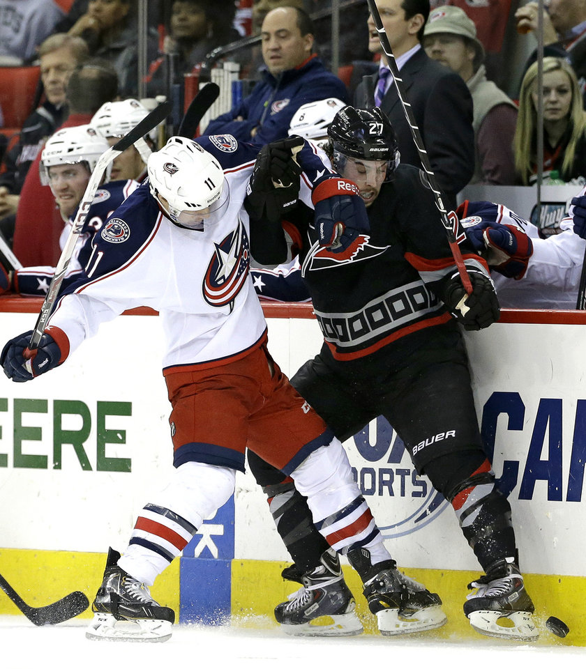 Photo - Carolina Hurricanes' Justin Faulk (27) and Columbus Blue Jackets' Matt Calvert (11) chase the puck during the second period of an NHL hockey game in Raleigh, N.C., Monday, Jan. 27, 2014. (AP Photo/Gerry Broome)