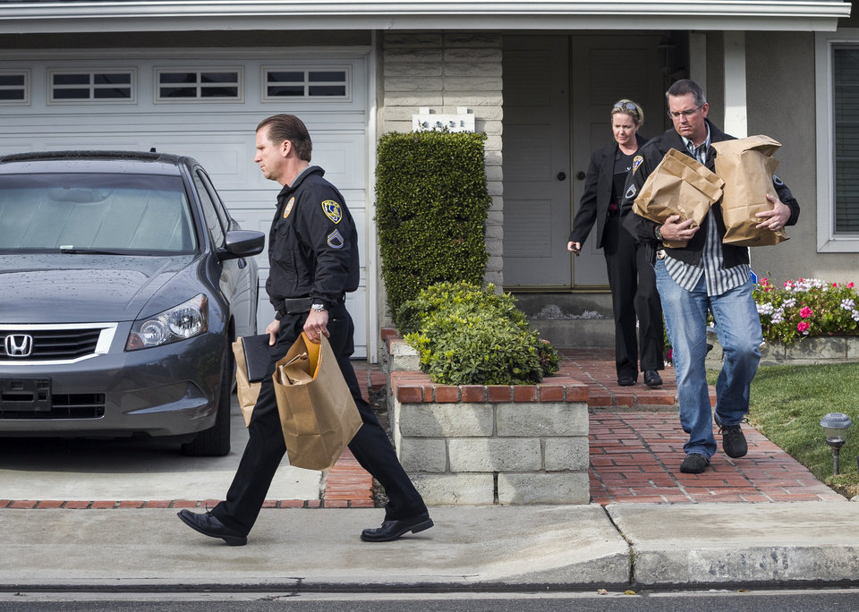Photo - Police investigators take away evidence from the home of the mother of fugitive suspect former Los Angeles police officer Christopher Dorner, in La Palma, Calif., on Friday, Feb. 8, 2013. Police agencies have launched a massive manhunt for Dorner, who is suspected of killing a couple over the weekend and opening fire on four officers early Thursday, killing one and critically wounding another, authorities said. (AP Photo/Damian Dovarganes)