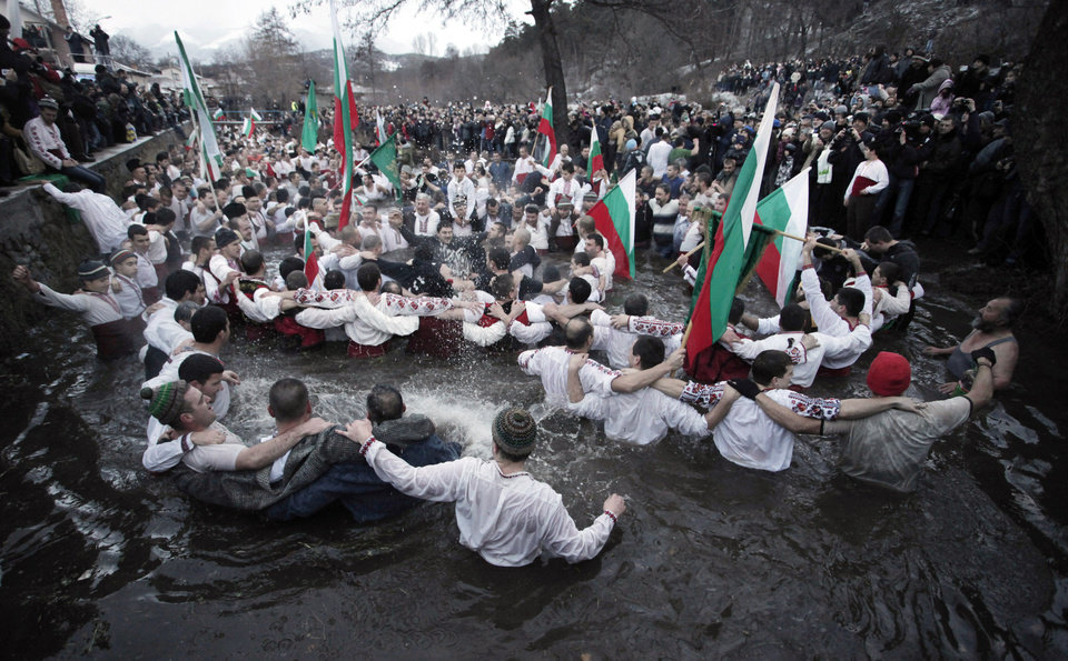Photo - Believers sing and dance in the icy waters of river Tundzha as they celebrate Epiphany day in the town of Kalofer, Bulgaria, Sunday, Jan. 6, 2013. Traditionally, an Eastern Orthodox priest throws a cross in the river and it is believed that the one who retrieves it will be healthy through the year. (AP Photo/Valentina Petrova)