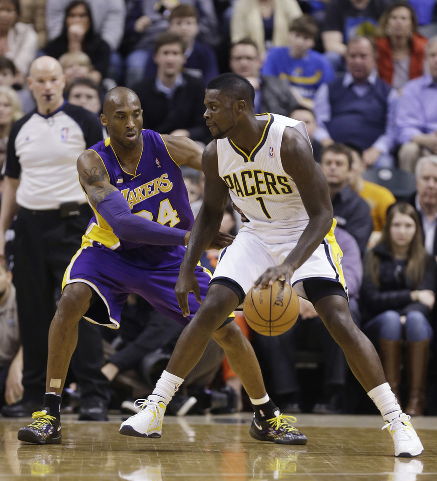 Photo - Los Angeles Lakers guard Kobe Bryant, left, defends Indiana Pacers guard Lance Stephenson during the first half of an NBA basketball game in Indianapolis, Friday, March 15, 2013.  (AP Photo/Michael Conroy)
