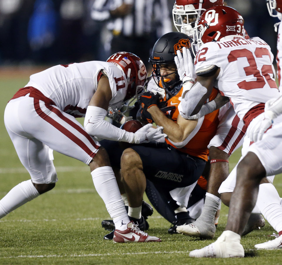 Photo - Oklahoma's Parnell Motley (11) forces a fumble by Oklahoma State's Braydon Johnson (8) in the first quarter during the Bedlam college football game between the Oklahoma State Cowboys (OSU) and Oklahoma Sooners (OU) at Boone Pickens Stadium in Stillwater, Okla., Saturday, Nov. 30, 2019. [Nate Billings/The Oklahoman]