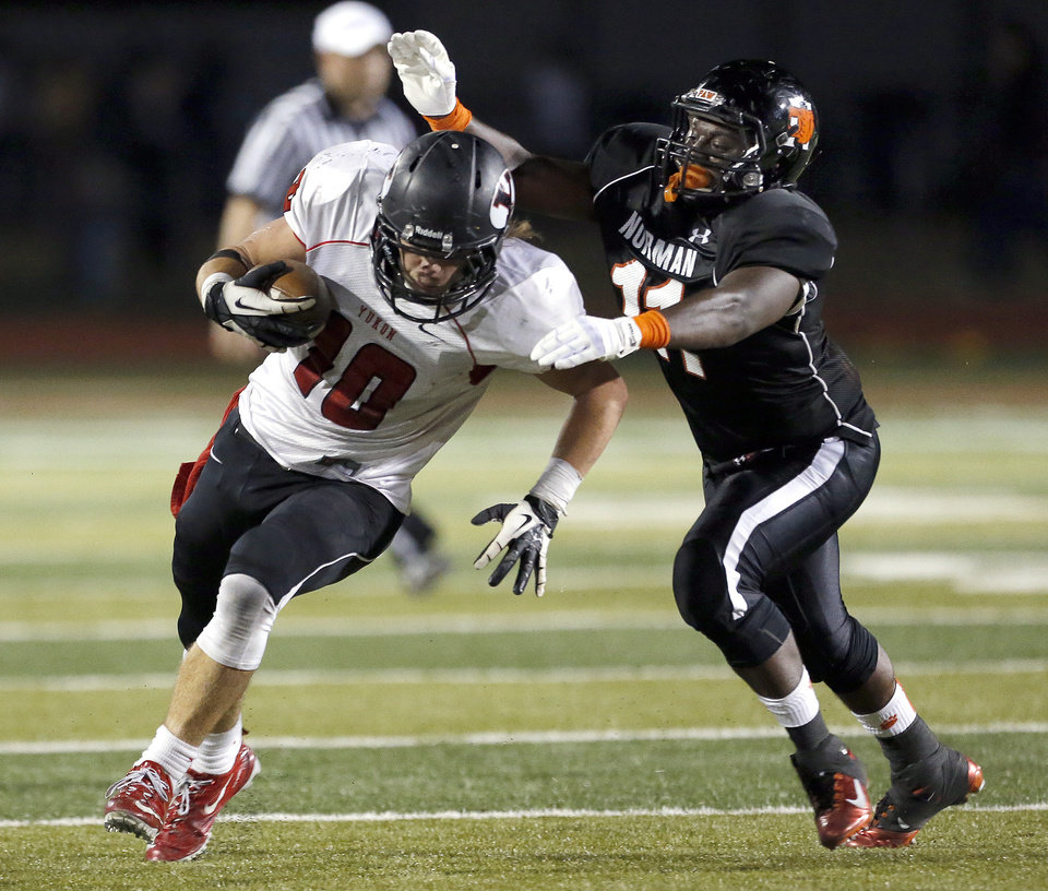 Photo - Yukon's Brandon Andraszek tries to get Blake Dean by Norman's during the high school football game between Norman and Yukon at Norman High School in Norman, Okla., Thursday, Nov. 8, 2012. Photo by Sarah Phipps, The Oklahoman