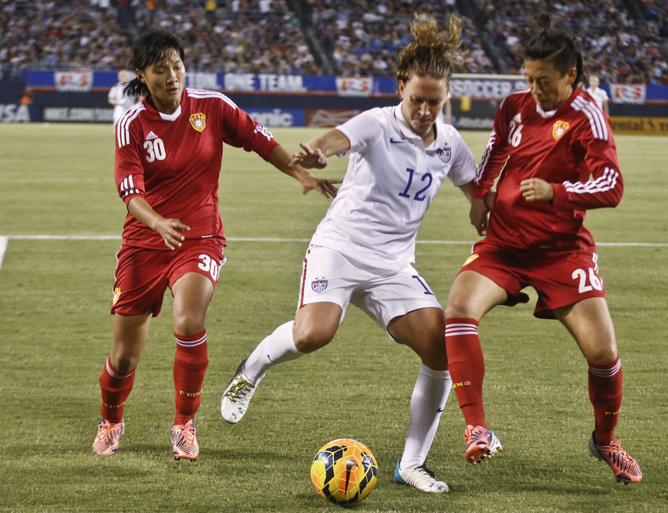 Photo - China defenders Li Dongna, right, and Liu Shanshan double-team U.S. midfielder Lauren Holiday during the first half of an international friendly soccer match Thursday, April 10, 2014, in San Diego. (AP Photo/Lenny Ignelzi)