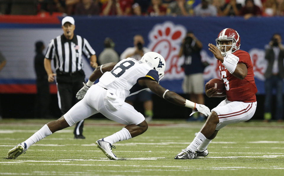Photo - Alabama quarterback Blake Sims (6) tries to get away from West Virginia safety Karl Joseph (8) in the first half of an NCAA college football game Saturday, Aug. 30, 2014, in Atlanta.  (AP Photo/Brynn Anderson)