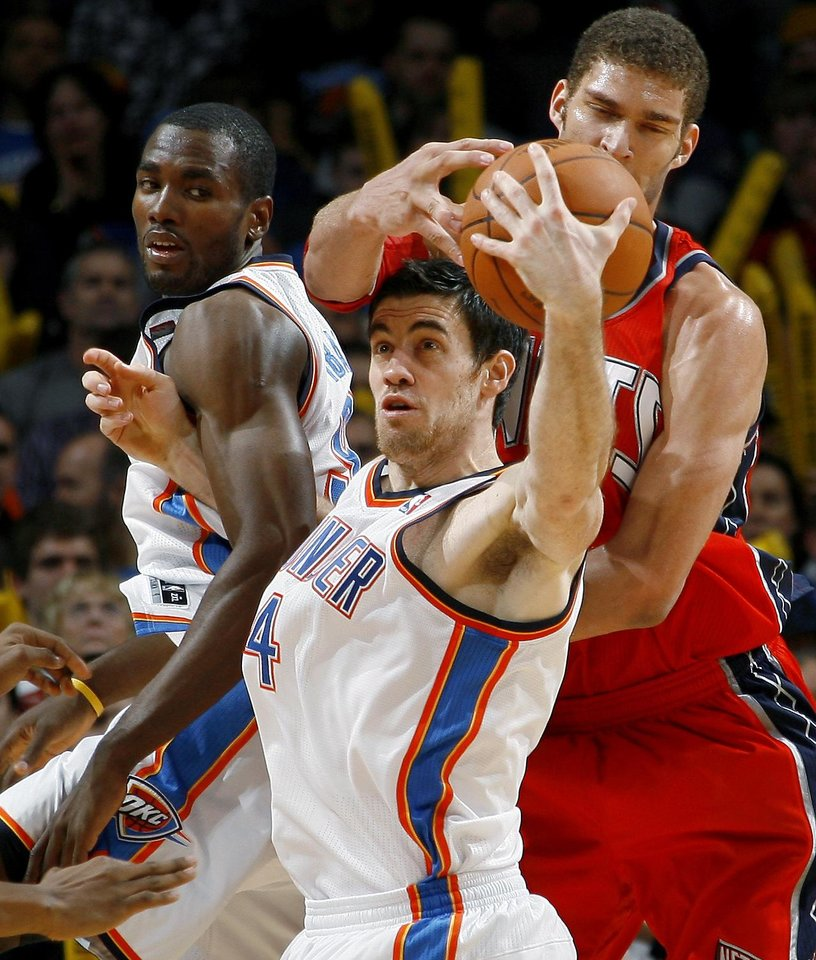 Photo - Oklahoma City's Nick Collison grabs the ball in front of New Jersey's Brook Lopez as Serge Ibaka watches during the NBA basketball game between the Oklahoma City Thunder and the New Jersey Nets at the Oklahoma City Arena, Wednesday, Dec. 29, 2010.  Photo by Bryan Terry, The Oklahoman