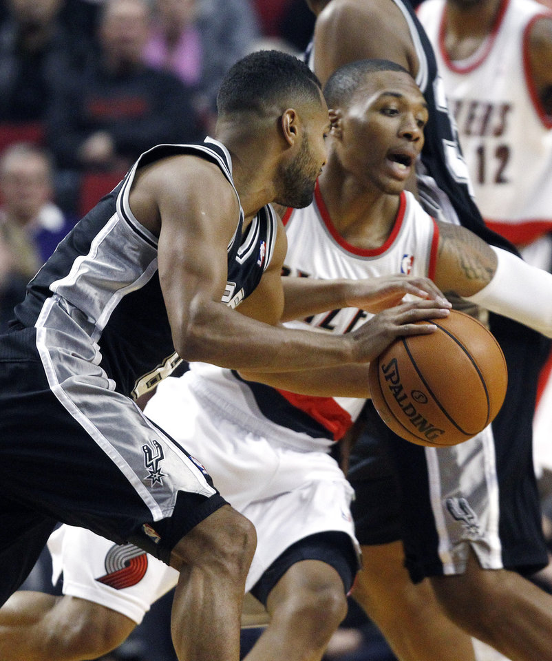 San Antonio Spurs guard Patty Mills, left, drives on Portland Trail Blazers guard Damian Lillard during the first half of their NBA basketball game in Portland, Ore., Saturday, Nov. 10, 2012. (AP Photo/Don Ryan)