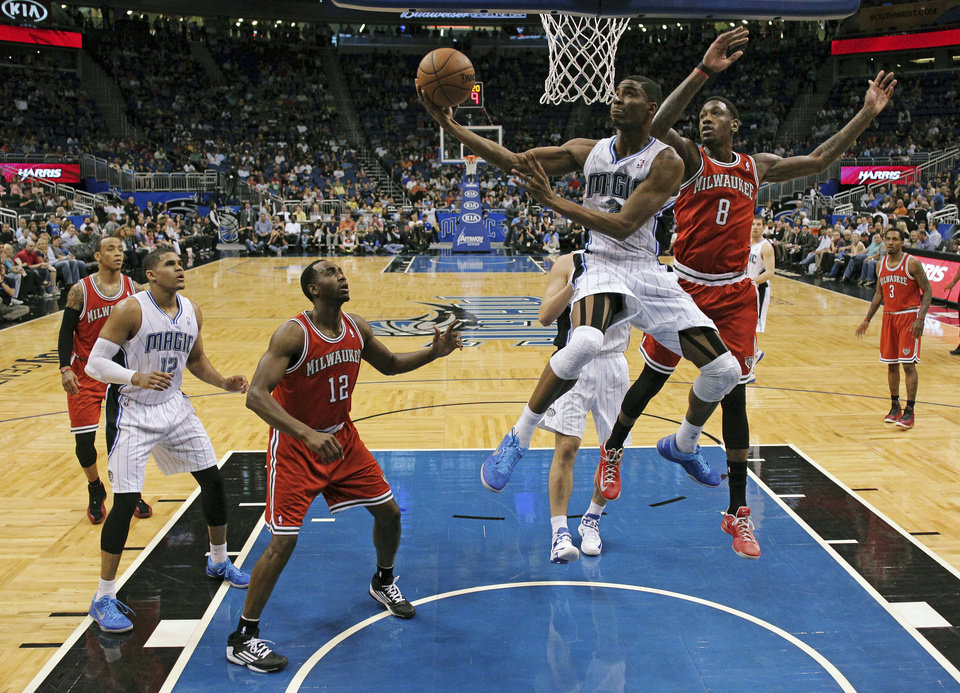 Photo - Orlando Magic's Maurice Harkless, center, shoots in front of Milwaukee Bucks' Larry Sanders (8) as Luc Richard Mbah a Moute (12), of Cameroon, and Magic's Tobias Harris, left, watch during the first half of an NBA basketball game, Wednesday, April 10, 2013, in Orlando, Fla. (AP Photo/John Raoux)