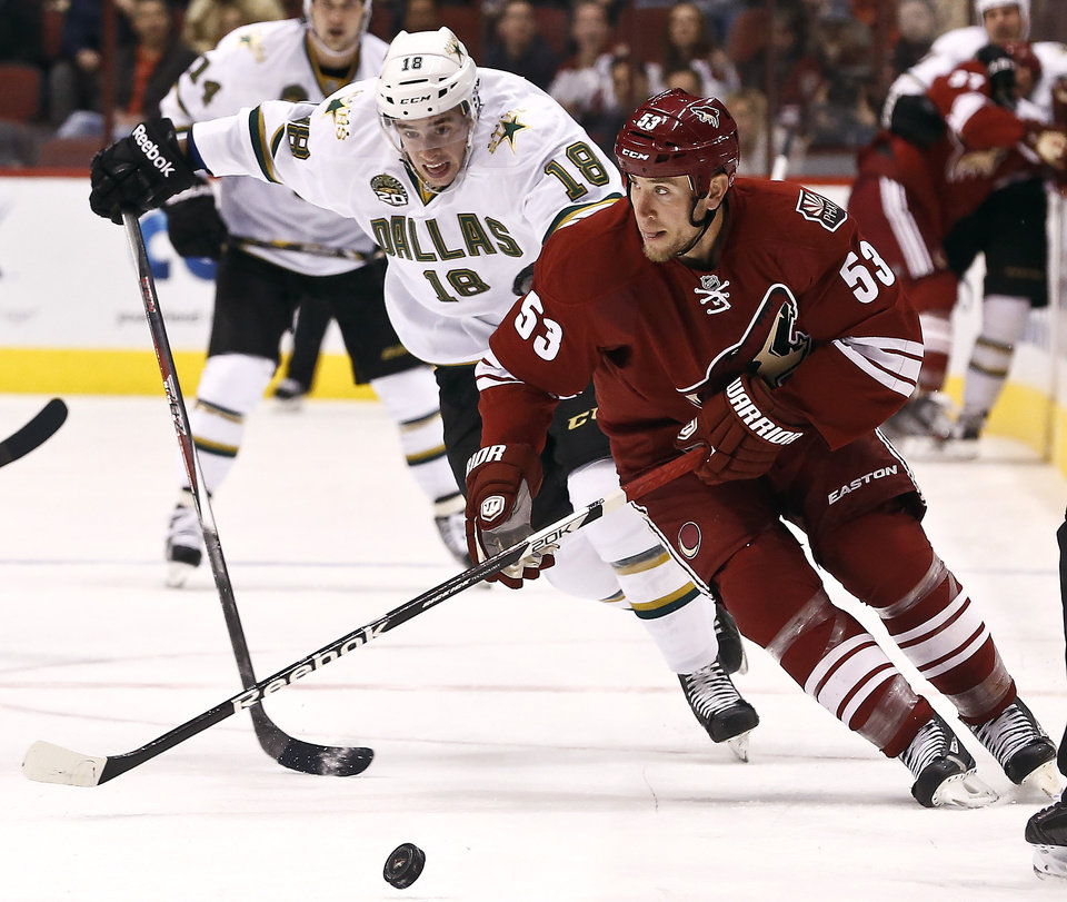Phoenix Coyotes\' Derek Morris (53) tries to keep the puck away from Dallas Stars\' Reilly Smith (18) during the first period of an NHL hockey game Saturday, Feb. 2, 2013, in Glendale, Ariz. (AP Photo/Ross D. Franklin)