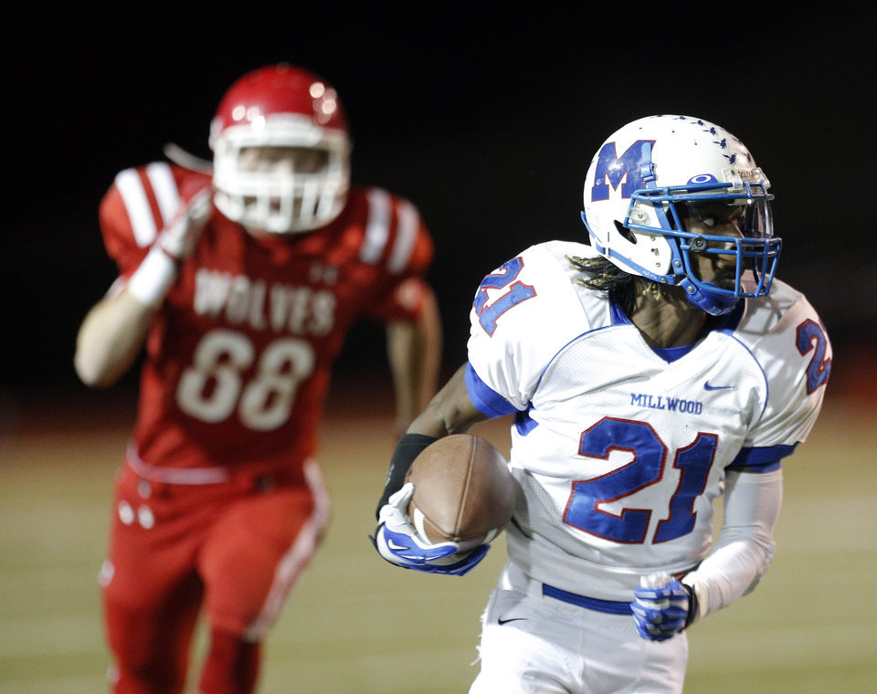 Photo - Millwood's Janari Glover rushes up field as Logan Conyers chases him during the Class 2A state football championship game between Davis and Millwood at Moore High School in Moore, Okla.,  Thursday, Dec. 19, 2013. Photo by Sarah Phipps, The Oklahoman