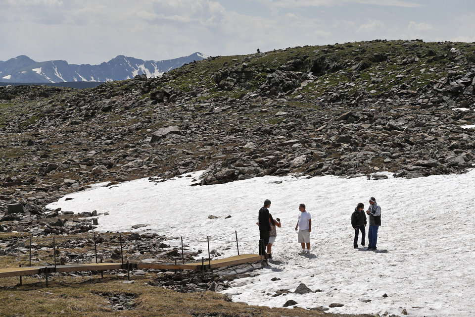 Photo - Visitors stand in a snowfield just off Trail Ridge Road, above tree-line at Rocky Mountain National Park, west of Estes Park, Colo., Monday, July 14, 2014. Lightning killed two people last weekend just miles apart in the popular park, where summer storms can close in quickly with deadly results. (AP Photo/Brennan Linsley)