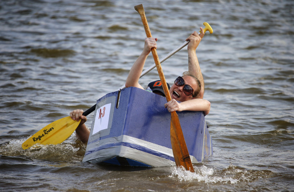 Photo -  First-time participants Rexi Phillips, front, and husband Mark Phillips, of Team Bolt, try to keep their boat afloat during the sixth annual Cardboard Boat Regatta at Arcadia Lake. PHOTO BY BRYAN TERRY, THE OKLAHOMAN   Bryan Terry -  THE OKLAHOMAN