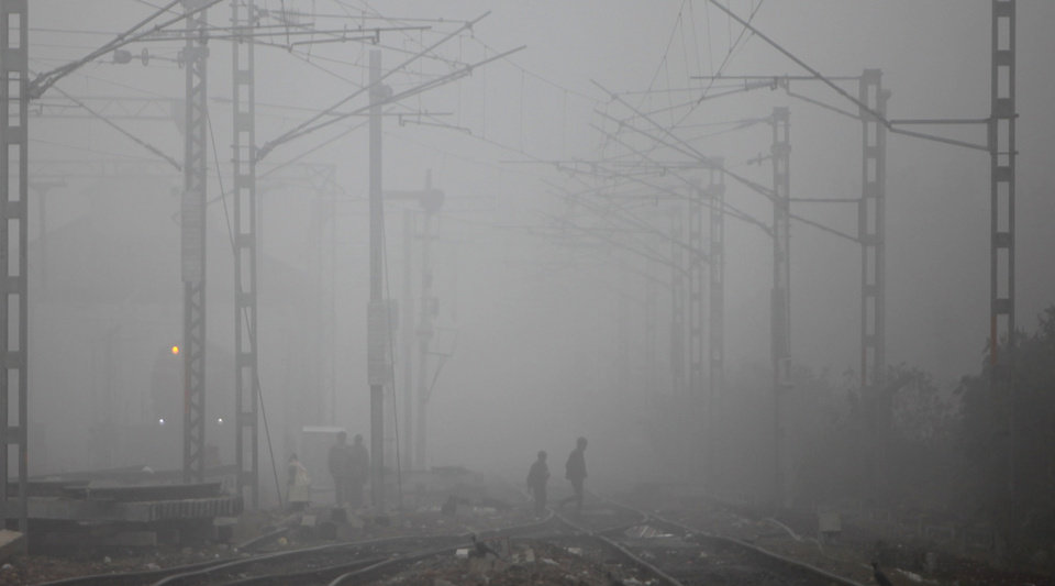 People walk across railway tracks in the fog in Jammu, India, Sunday, Dec. 30, 2012. North India continues to face extreme weather conditions with dense fog affecting flights and trains. (AP Photo/Channi Anand)