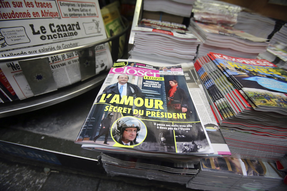 Photo - The French magazine Closer with photos of French President Francois Hollande and French actress Julie Gayet on its front page,  is presented in a newspaper stall on the Champs Elysee Avenue in Paris, Friday Jan. 10, 2013. French President Francois Hollande is threatening legal action over the magazine report saying he is having a secret affair with the French actress Julie Gayet. Hollande, in a statement obtained by The Associated Press, says he