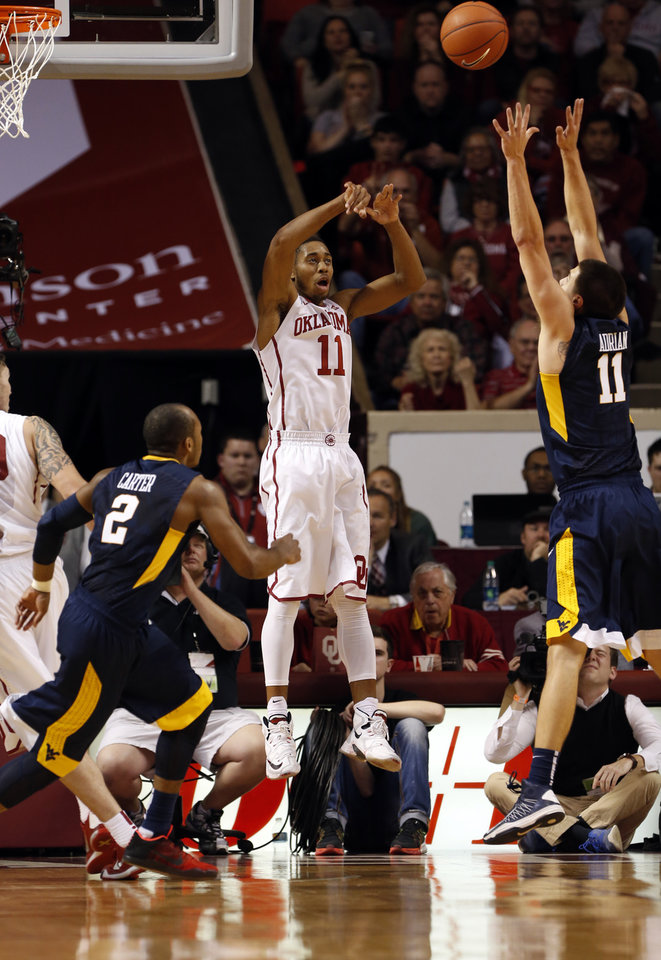 Photo - Oklahoma's Isaiah Cousins (11) throws over the full court press and West Virginia's Jevon Carter (2) and Nathan Adrian (11) as the University of Oklahoma Sooner (OU) men play the West Virginia Mountaineers (WV) in NCAA, college basketball at The Lloyd Noble Center on Jan. 16, 2016 in Norman, Okla. Photo by Steve Sisney, The Oklahoman