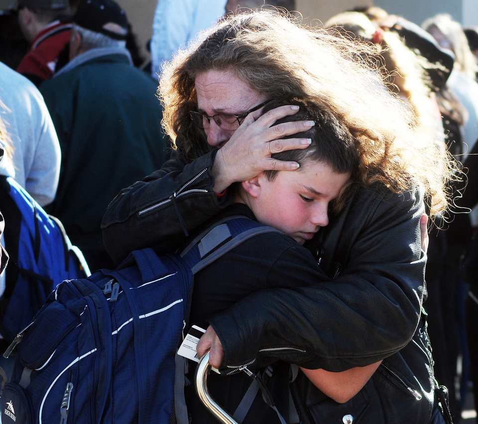 Photo - A woman hugs a student at a staging ground set up at the Roswell Mall following a shooting at Berrendo Middle School, Tuesday, Jan. 14, 2014, in Roswell, N.M. A shooter opened fire at the middle school, injuring at least two students before being taken into custody. Roswell police said the school was placed on lockdown, and the suspected shooter was arrested. (AP Photo/Roswell Daily Record, Mark Wilson)