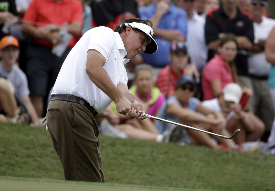 Photo - Phil Mickelson chips onto the sixth green during the first round of the Honda Classic golf tournament on Thursday, Feb. 27, 2014, in Palm Beach Gardens, Fla. (AP Photo/Lynne Sladky)