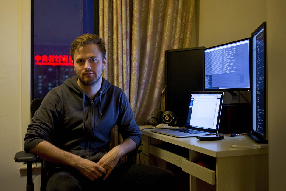 """Photo - In this Sunday, June 1, 2014 photo, Nils Pihl sits next to a work station at his apartment, which he converted to an office in Beijing, China. Pihl has spent 18 months building what he calls cutting-edge software to crunch """"really big data sets."""" But instead of going to Silicon Valley, the 27-year-old Swede and his four colleagues have been working on his invention from a small apartment overlooking smoggy northwest Beijing. (AP Photo/Andy Wong)"""