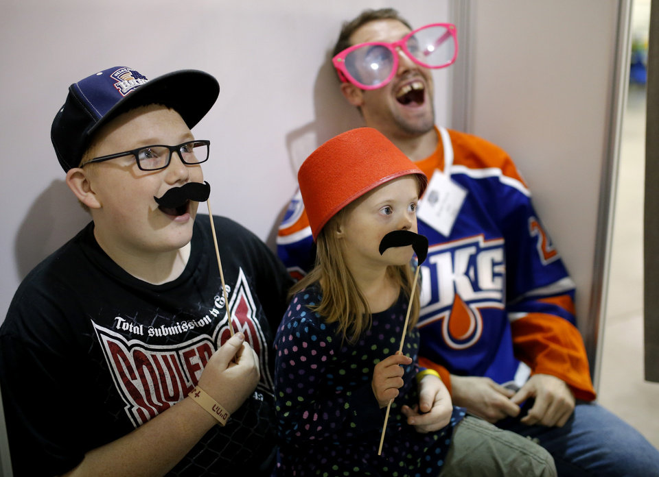 Photo - Mia Dickinson ,6, poses for a photo in a photo booth with her Barons Buddy, Brad Hunt, and her brother Tanner, 13, during a Barons Buddies event with the Oklahoma City Barons and Special Olympians in Oklahoma City, Tuesday, November 5, 2013. The Special Olympians and their families were introduced to the Barons player that they will paired with throughout the year. Photo by Bryan Terry, The Oklahoman