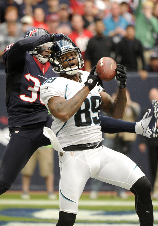 Photo -   Jacksonville Jaguars' Marcedes Lewis (89) is grabbed by Houston Texans' Troy Nolan during the first quarter of an NFL football game, Sunday, Nov. 18, 2012, in Houston. (AP Photo/Dave Einsel)
