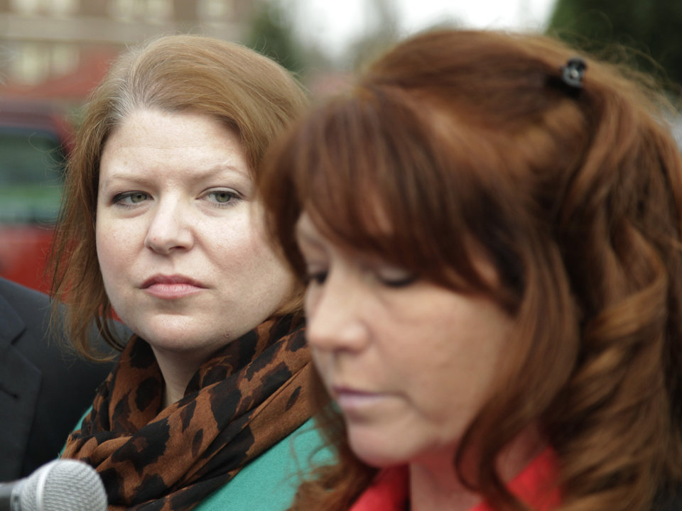Photo -   Kari Bales, left, listens as her sister, Stephanie Tandberg, right, reads a statement to reporters Tuesday, Nov. 13, 2012, outside the building housing a military courtroom on Joint Base Lewis McChord in Washington state, where a preliminary hearing ended Tuesday for Kari's husband, U.S. Army Staff Sgt. Robert Bales. Bales is accused of 16 counts of premeditated murder and six counts of attempted murder for a pre-dawn attack on two villages in Kandahar Province in Afghanistan in March of 2012. (AP Photo/Ted S. Warren)