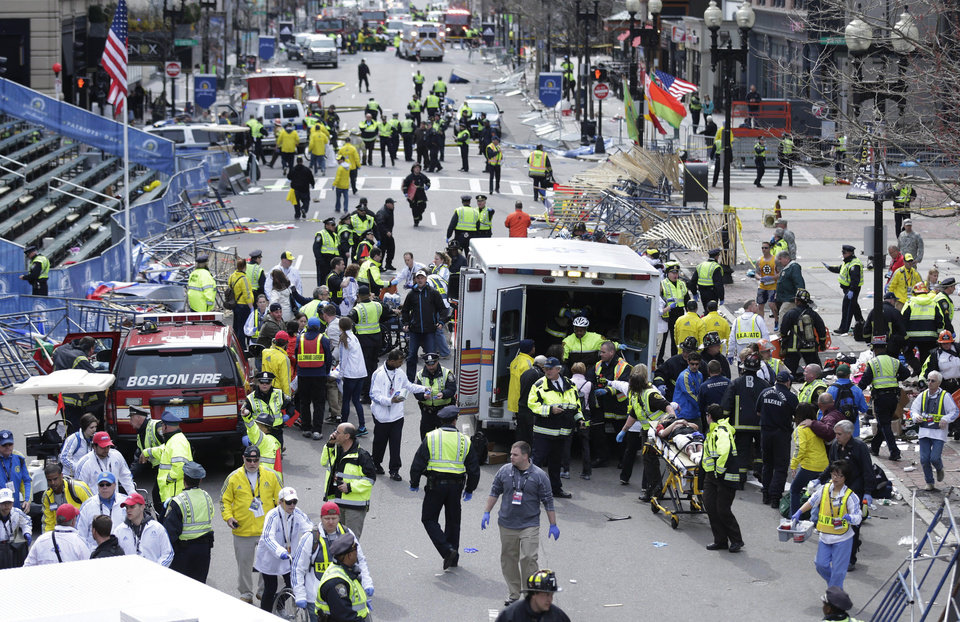 Photo - FILE - In this April 15, 2013 file photo, medical workers aid injured people at the finish line of the 2013 Boston Marathon following a bomb explosion in Boston, Monday, April 15, 2013.  In addition to Tamerlan Tsarnaev, who died after a gunfight with police, and his brother, Dzhokhar Tsarnaev, who was captured and lies in a hospital prison, three more suspects in the bombings were taken into custody, Boston police said Wednesday, May 1, 2013.  (AP Photo/Charles Krupa, File)