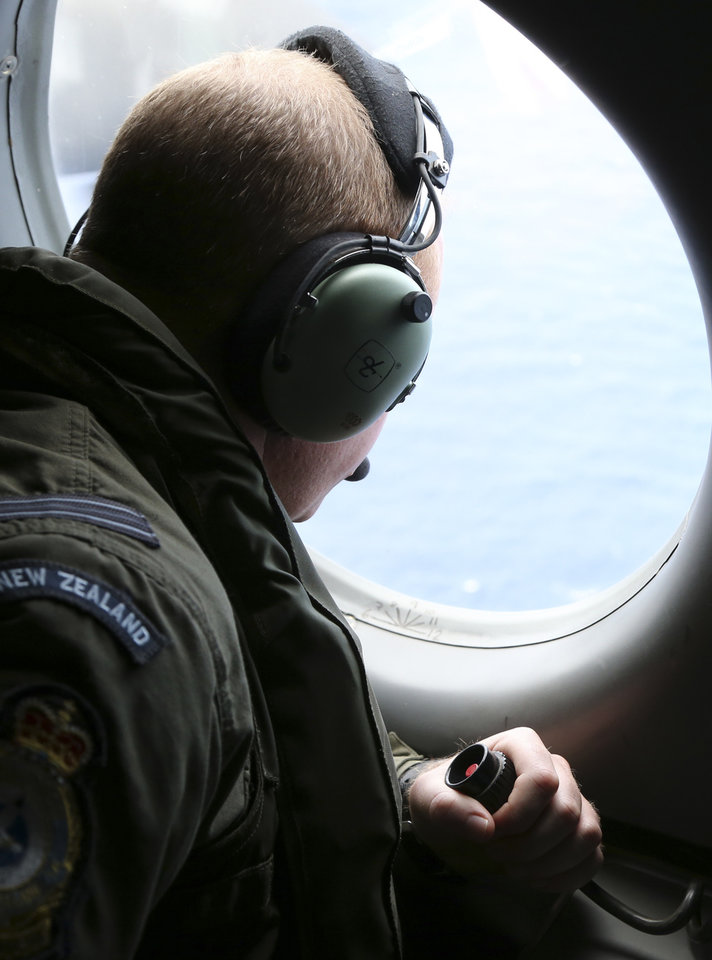 Photo - Royal New Zealand Air Force tactical coordinator Flight Lt.  Pete Jackson looks out a window on his P-3 Orion while searching for missing Malaysia Airlines Flight MH370 in Perth, Australia, Monday, March 31, 2014. (AP Photo/Rob Griffith, Pool)