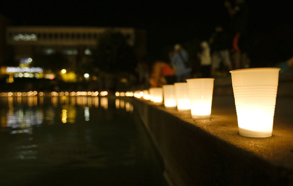 Photo - Candles line a wall around a reflection pond at the University of Central Florida, Wednesday, Sept. 3, 2014, in Orlando, Fla., to honor Steven Sotloff, the second American journalist to be beheaded by the Islamic State militant group in two weeks. Sotloff attended the University of Central Florida between 2002 and 2004. (AP Photo/John Raoux)
