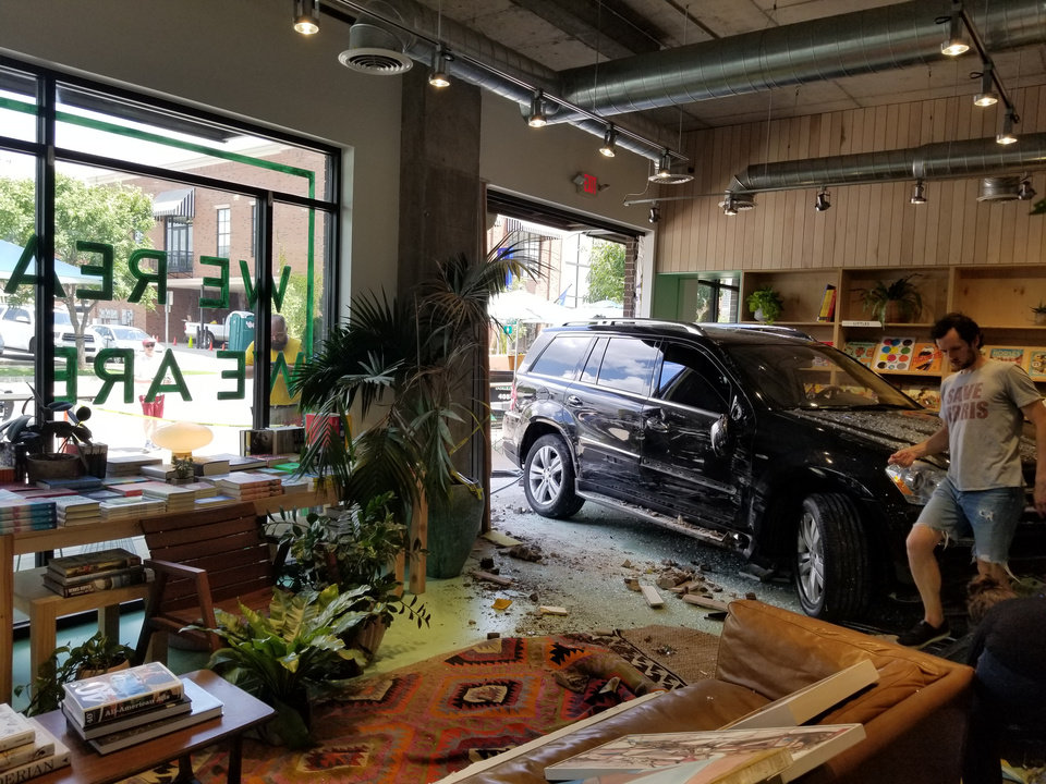 Photo - A black Mercedes-Benz BlueTeC SUV crashed into Commonplace Bookstore in Midtown Oklahoma City on Tuesday, July 10, 2018. (Photo by Ben Felder)