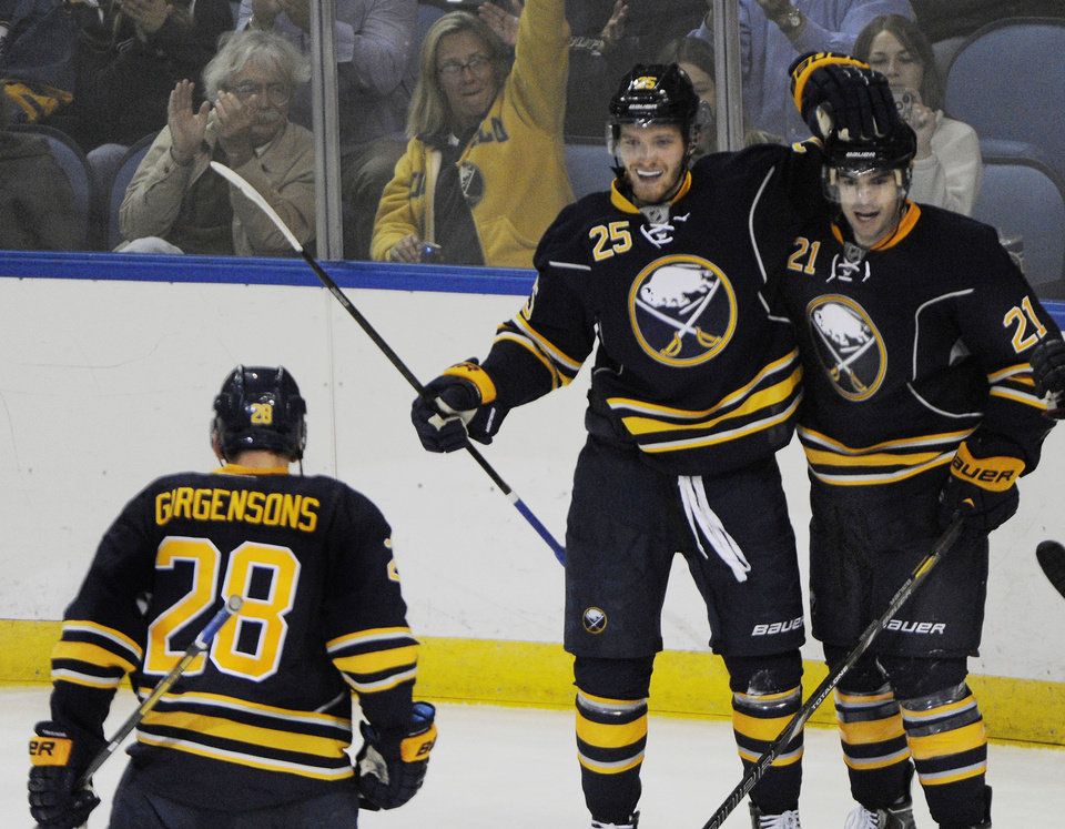 Photo - Buffalo Sabres' Mikhail Grigorenko (25) celebrates his goal with teammates Zemgus Girgensons (28) and Drew Stafford (21) during the third period of an NHL hockey preseason game against the Columbus Blue Jackets in Buffalo, N.Y., Wednesday, Sept. 25, 2013. Buffalo won 3-0. (AP Photo/Gary Wiepert)
