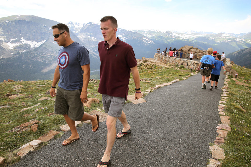 Photo - Visitors walk a short trail at a scenic overlook off Trail Ridge Road, above tree-line at Rocky Mountain National Park, west of Estes Park, Colo., Monday, July 14, 2014. Lightning killed two people last weekend just miles apart in the popular park, where summer storms can close in quickly with deadly results. (AP Photo/Brennan Linsley)