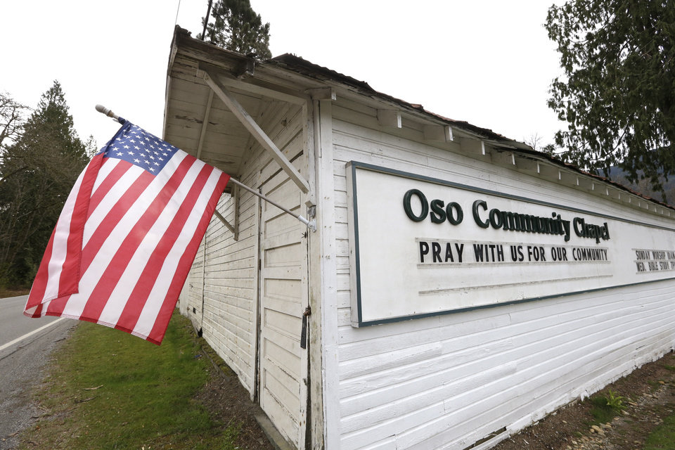 Photo - A flag flies from a small church off the highway leading to the scene of a deadly mudslide Monday morning, March 24, 2014, near Oso, Wash. Officials said that there are currently 108 names of people who have been reported missing or are unaccounted for from the Saturday morning slide, but cautioned the figure would likely decline dramatically. Eight people are so far confirmed dead from the one-square mile slide that destroyed about 30 homes and critically injured several people. (AP Photo/Elaine Thompson)