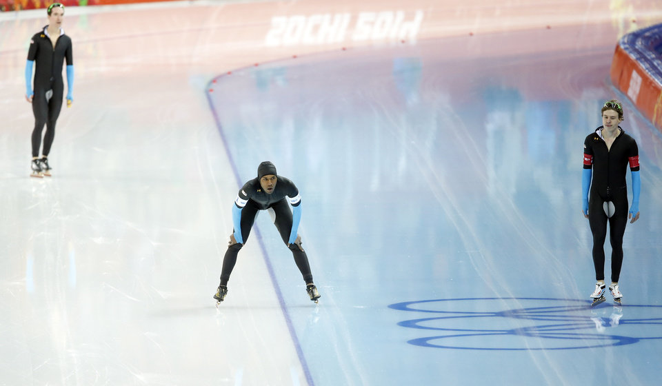 Photo - The U.S. speedskating team Shani Davis, center, Brian Hansen, right, and Jonathan Kuck, top left, catch their breath after competing in the men's speedskating team pursuit quarterfinals at the Adler Arena Skating Center during the 2014 Winter Olympics in Sochi, Russia, Friday, Feb. 21, 2014. (AP Photo/Patrick Semansky)