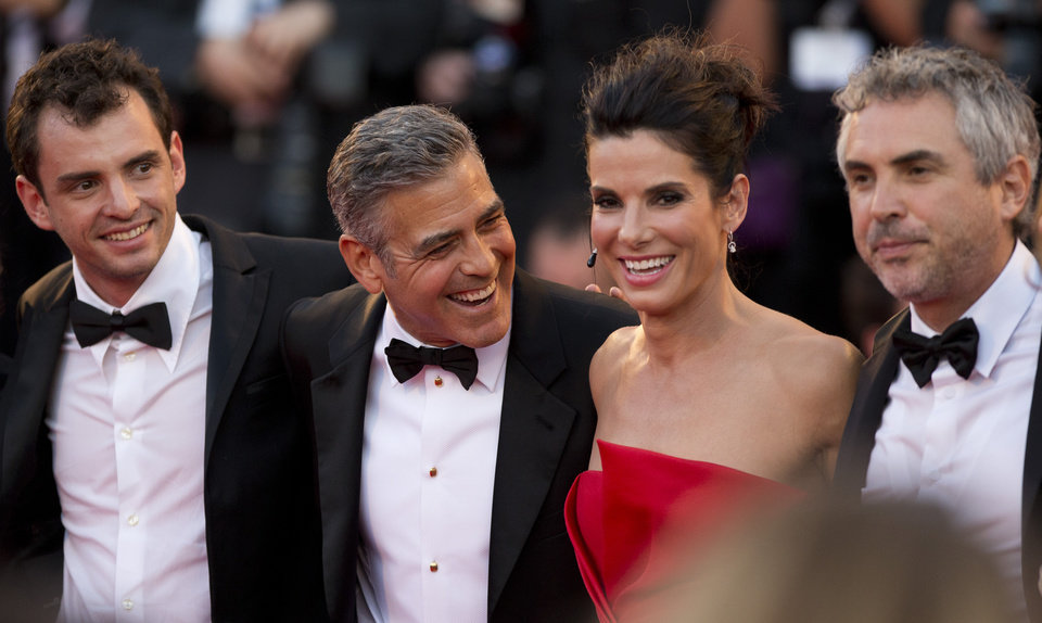 "FILE - In this Aug. 28, 2013, from left, screenwriter Jonas Cuaron, actors Sandra Bullock, George Clooney and director Alfonso Cuaron pose for photographers as they arrive for the screening of ""Gravity"" at the 70th edition of the Venice Film Festival, in Venice, Italy. Bullock says making the lost-in-space movie ��Gravity�� with director Alfonso Cuaron was her ��best life decision�� ever.  Bullock��s priority had been spending time with her son, who is now 3, and Cuaron assured her that she wouldn��t miss anything on the film, which also features George Clooney and lands in US theatres on Friday, Oct. 4, 2013. (AP Photo/David Azia, File)"
