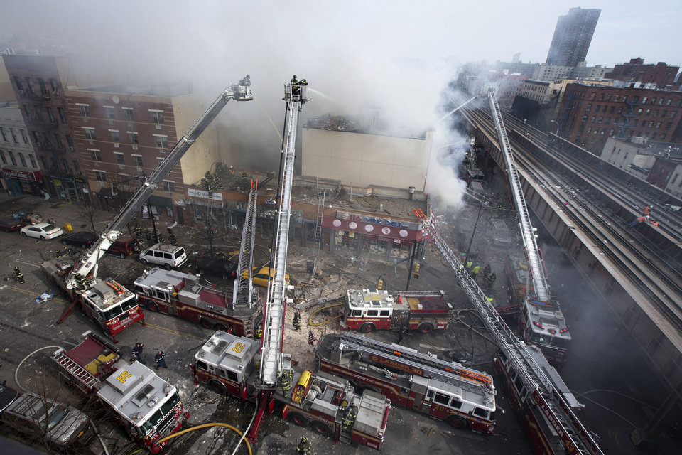 Photo - Firefighters battle a fire after a building collapses in the East Harlem neighborhood of New York, Wednesday, March 12, 2014 (AP Photo/John Minchillo)
