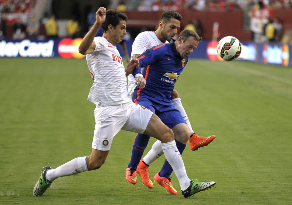 Photo - Manchester United's Wayne Rooney, center, battles for the ball against Inter Milan's Andrea Ranocchia, left, and Danilo D'Ambrosio during the first half of a soccer game at  the 2014 Guinness International Champions Cup, Tuesday, July 29, 2014, in Landover, Md. Manchester United won 5-3 in a penalty kick shootout. (AP Photo/Luis M. Alvarez)