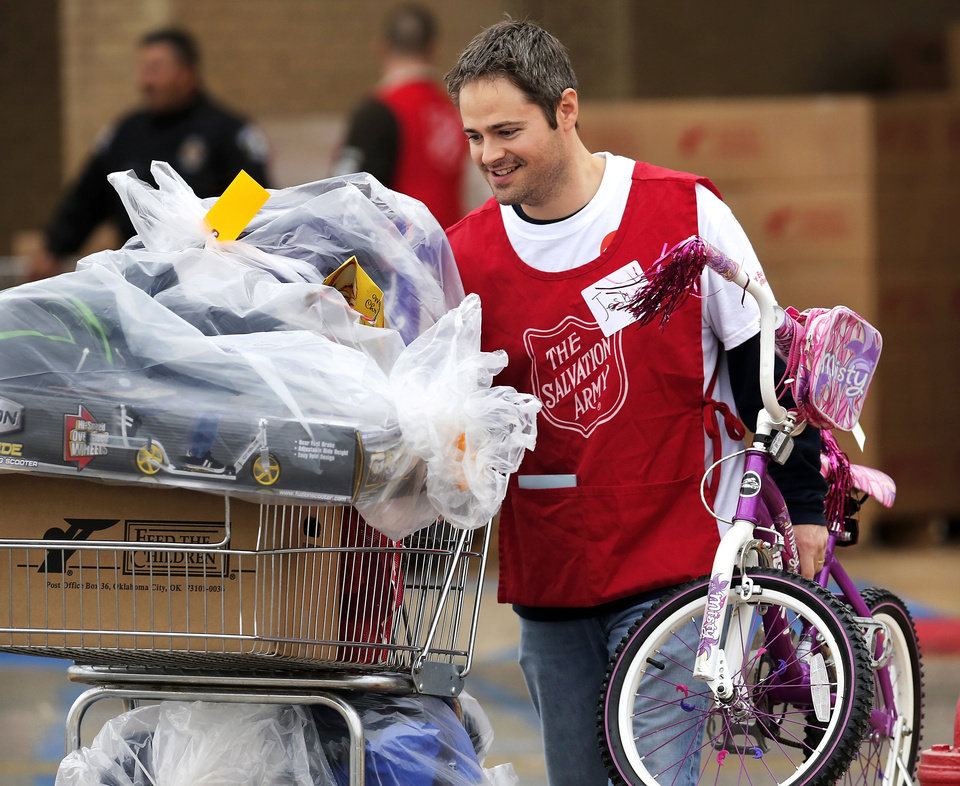 Josh Fausset, a volunteer from OG&E, pushes a cart filled with bags of toys and carries a girl\'s bicycle out of Crossroads Mall to a client\'s car. The Salvation Army and Feed the Children teamed to distribute bicycles and toys for children, and handed out boxes of food for families at their annual distribution event Wednesday, Dec. 19, 2012. Salvation Army officials said 100 volunteers helped make the event go smoothly. The volunteers loaded bags of toys and bikes into vehicles of clients who had been pre-approved for assistance. Many of the gifts were provided through the Salvation Army\'s Angel Tree program Photo by Jim Beckel, The Oklahoman