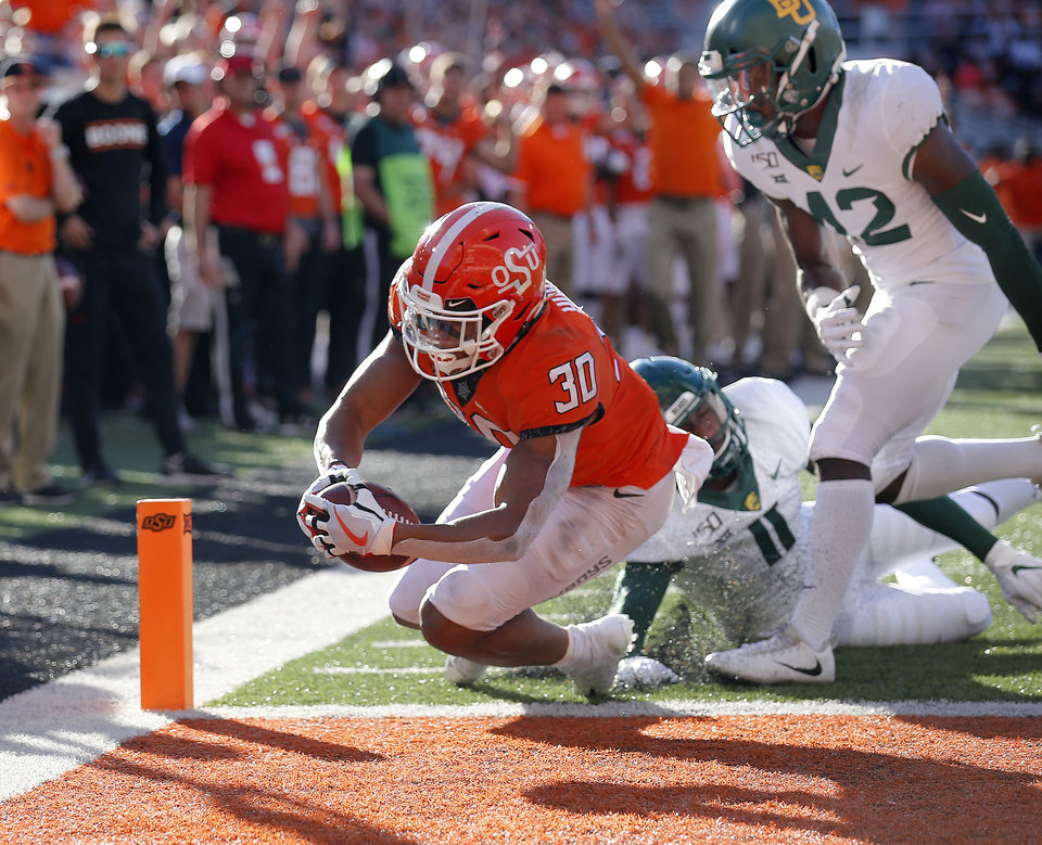 Photo - Oklahoma State's Chuba Hubbard (30) scores a touchdown as Baylor's Jameson Houston (11) and Jairon McVea (42) defend in the third quarter during the college football game between Oklahoma State University and Baylor at Boone Pickens Stadium in Stillwater, Okla., Saturday, Oct. 19, 2019. Baylor won 45-27. [Sarah Phipps/The Oklahoman]