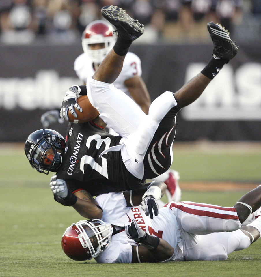 Photo - Isaiah Pead (23) is tackled by Tony Jefferson (1) during the first half of the college football game between the University of Oklahoma Sooners (OU) and the University of Cincinnati Bearcats (UC) at Paul Brown Stadium on Saturday, Sept. 25, 2010, in Cincinnati, Ohio.   Photo by Steve Sisney, The Oklahoman