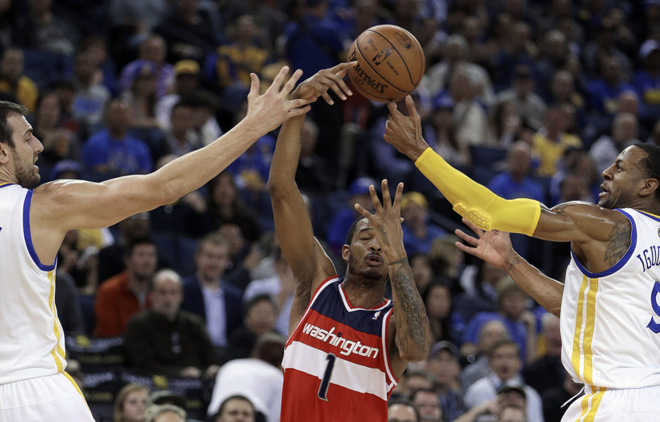 Photo - Washington Wizards' Trevor Ariza, center, fights for a loose ball with Golden State Warriors' Andrew Bogut, left, and Andre Iguodala, right, during the first half of an NBA basketball game, Tuesday, Jan. 28, 2014, in Oakland, Calif. (AP Photo/Ben Margot)