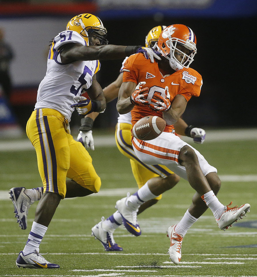 Photo - Clemson wide receiver DeAndre Hopkins (6) misses catch under pressure from LSU linebacker Lamin Barrow (57) during the second half of the Chick-fil-A Bowl NCAA college football game, Monday, Dec. 31, 2012, in Atlanta. (AP Photo/John Bazemore)