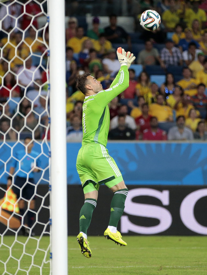 Photo - Russia's goalkeeper Igor Akinfeev catches the ball in front of the goal mouth during the group H World Cup soccer match between Russia and South Korea at the Arena Pantanal in Cuiaba, Brazil, Tuesday, June 17, 2014.  (AP Photo/Ivan Sekretarev)
