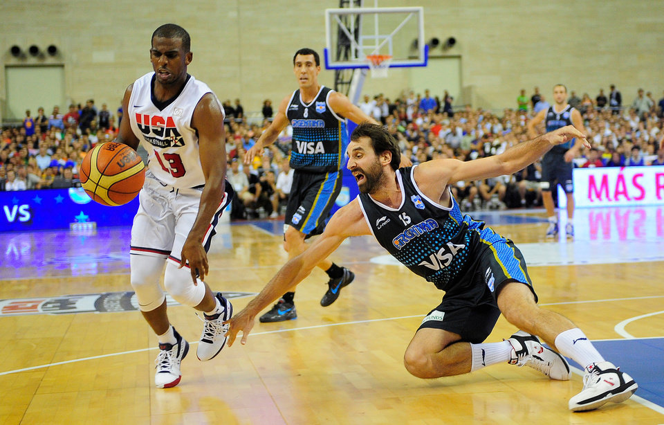 Photo - Chris Paul of the U.S. men's senior national team, left, drives past Federico Kammerichs of Argentina during their Pre-Olympic friendly basketball match at the Palau Sant Jordi in Barcelona, Spain, Sunday, July 22, 2012. (AP Photo/Manu Fernandez) ORG XMIT: MF114