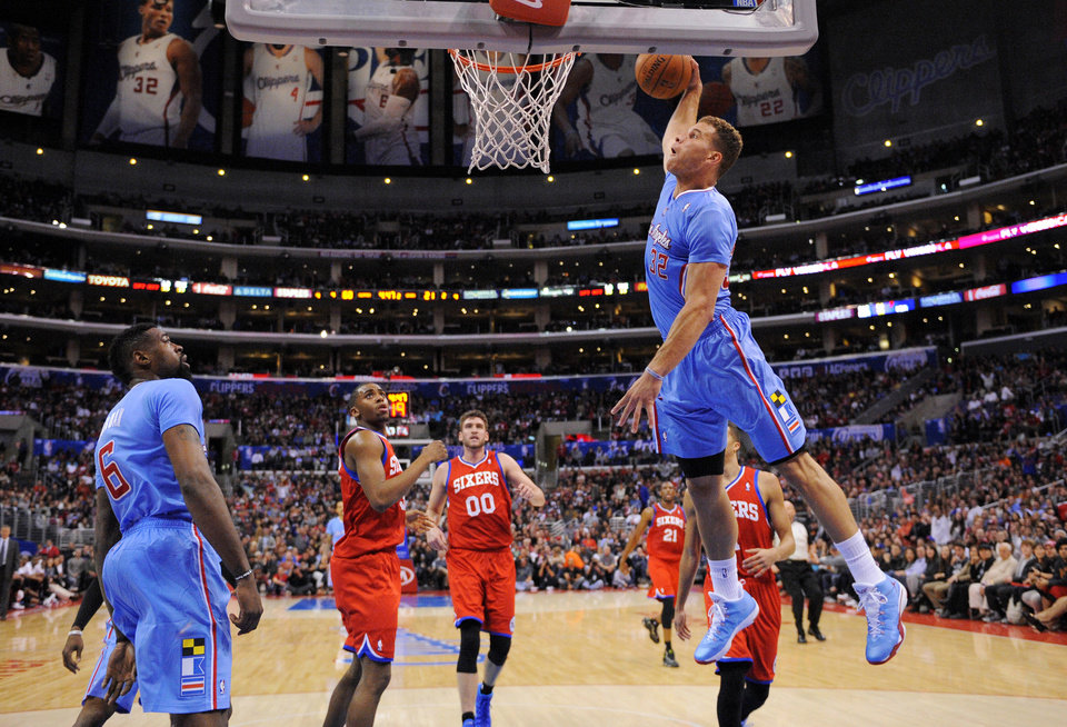 Photo - Los Angeles Clippers forward Blake Griffin, right, goes up for a dunks as teammate center DeAndre Jordan, left, stands near along with Philadelphia 76ers guard Hollis Thompson, second from left, and center Spencer Hawes, third from left, during the first half of an NBA basketball game, Sunday, Feb. 9, 2014, in Los Angeles. (AP Photo/Mark J. Terrill)